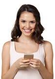 Mujer que manda un SMS con su teléfono Imagen de archivo libre de regalías
