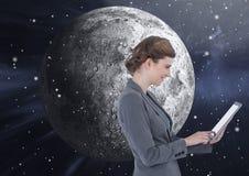 Mujer que manda un SMS delante de la luna Foto de archivo libre de regalías
