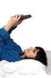 Mujer que manda un SMS en cama Imagenes de archivo