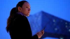 Mujer que manda un SMS en el smartphone que se opone a paisaje urbano moderno de la noche metrajes
