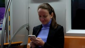 Mujer que manda un SMS en el smartphone que se sienta en el coche de subterráneo almacen de metraje de vídeo