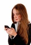 Mujer que manda un SMS en el teléfono Imagen de archivo libre de regalías
