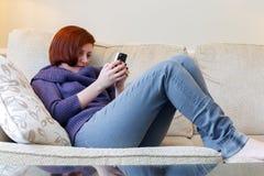 Mujer que manda un SMS en el teléfono celular Imagen de archivo