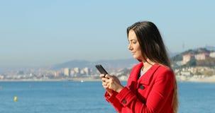 Mujer que manda un SMS en el teléfono en la playa en invierno