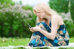 Mujer que manda un SMS en el teléfono móvil Foto de archivo libre de regalías