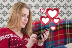 Mujer que manda un SMS en el teléfono móvil con los corazones rojos digital generados Fotos de archivo libres de regalías