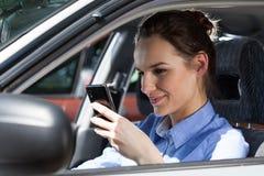 Mujer que manda un SMS en el teléfono móvil en el coche Foto de archivo