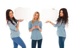 Mujer que manda un SMS en el teléfono y sus amigos que llevan a cabo burbujas del discurso Foto de archivo libre de regalías