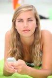 Mujer que manda un SMS en la playa. Imagenes de archivo