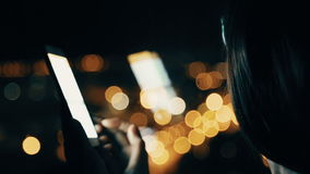 Mujer que manda un SMS en Smartphone en fondo de la ciudad almacen de video