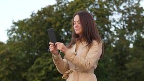Mujer que manda un SMS en smartphone y que sonríe feliz almacen de video