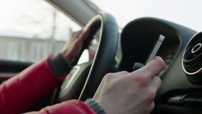 Mujer que manda un SMS mientras que conduce un coche almacen de metraje de vídeo