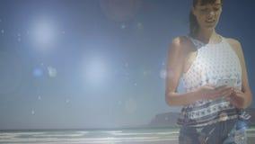Mujer que manda un SMS por la playa almacen de metraje de vídeo