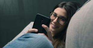 Mujer que manda un SMS tarde en la noche Fotos de archivo libres de regalías