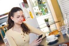 Mujer que manda un SMS a un mensaje con su teléfono elegante Fotografía de archivo libre de regalías
