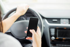 Mujer que manda un SMS y que conduce Imagen de archivo libre de regalías