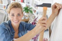 Mujer que martilla un clavo foto de archivo libre de regalías
