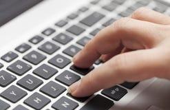 Mujer que mecanografía en el ordenador portátil Fotos de archivo libres de regalías