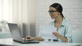 Mujer que mecanografía en el ordenador portátil en casa, pagando utilidades o comprobando correspondencia almacen de video