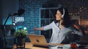 Mujer que mecanografía en el ordenador portátil que escucha la música en auriculares en oficina oscura en la noche almacen de metraje de vídeo