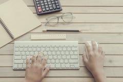 Mujer que mecanografía en el teclado de ordenador Imágenes de archivo libres de regalías
