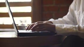 Mujer que mecanografía en el teclado del ordenador portátil en una cafetería almacen de video