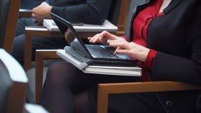 Mujer que mecanografía en un ordenador portátil durante una conferencia metrajes