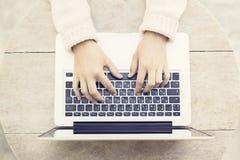 Mujer que mecanografía en un ordenador portátil en la tabla de madera al aire libre Imágenes de archivo libres de regalías