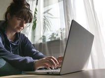 Mujer que mecanografía en un teclado del ordenador portátil, sentándose en casa por la ventana imagen de archivo