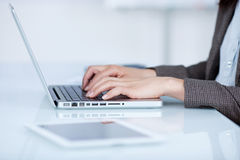 Mujer que mecanografía en su ordenador portátil Imágenes de archivo libres de regalías