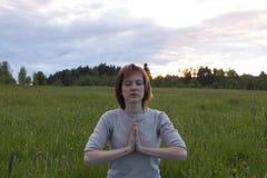 Mujer que medita en actitud del loto en la puesta del sol Fotografía de archivo libre de regalías
