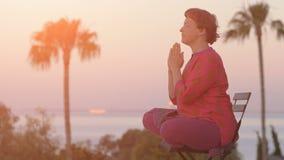 Mujer que medita en actitud del loto en la salida del sol Forma de vida sana Meditación de la mañana Concepto de la meditación de almacen de metraje de vídeo