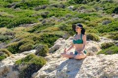 Mujer que medita en la actitud de Lotus en las rocas el concepto de resto, relajación, paz espiritual, yoga foto de archivo