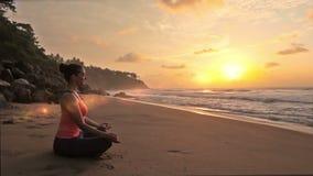 Mujer que medita en la playa en puesta del sol almacen de metraje de vídeo