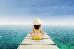 Mujer que medita en la playa serena Foto de archivo