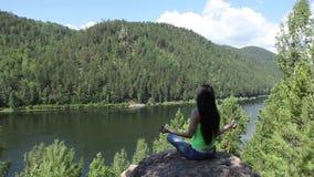 Mujer que medita en la postura del loto que hace yoga encima de la monta?a en una roca almacen de video
