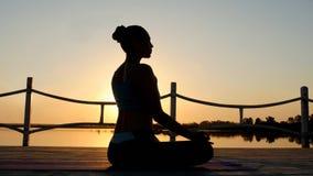 Mujer que medita en loto de la actitud sobre el sol anaranjado almacen de video