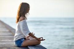 Mujer que medita en Lotus Pose en el embarcadero Imágenes de archivo libres de regalías