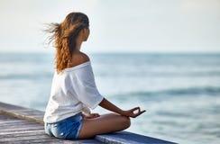 Mujer que medita en Lotus Pose en el embarcadero Fotografía de archivo libre de regalías