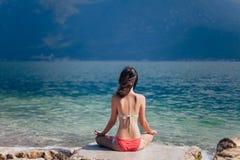 Mujer que medita en Lotus Pose en la playa hermosa del la de la montaña Imágenes de archivo libres de regalías