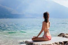 Mujer que medita en Lotus Pose en la playa hermosa del la de la montaña Imagenes de archivo