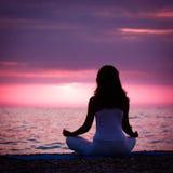 Mujer que medita en Lotus Position por el mar Imagenes de archivo