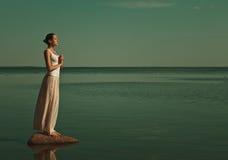 Mujer que medita en una actitud de la yoga Fotografía de archivo