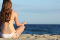 Mujer que medita yoga en la playa en verano Foto de archivo