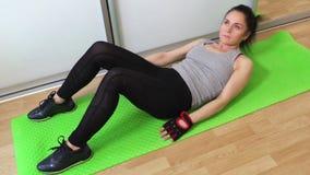 Mujer que mezcla los diversos ejercicios de la aptitud para los ABS de la estructura almacen de video