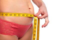 Mujer que mide el abdomen gordo Fotografía de archivo libre de regalías