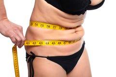 Mujer que mide el abdomen gordo Fotos de archivo libres de regalías