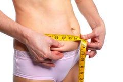 Mujer que mide el abdomen gordo Imagen de archivo libre de regalías