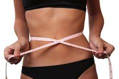 Mujer que mide su cintura Imagenes de archivo