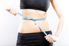 Mujer que mide su cintura, concepto de la pérdida de peso Fotografía de archivo libre de regalías